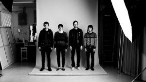 Mustavalkoinen kuva, jossa bändin jäsenet seisovat kuvaustaustan päällä. He ovat valaistu isolla, oikealla olevalla tasovalolla.