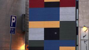 Väripaneleista koostuva tilataideteos Taideteollisen korkeakoulun seinässä