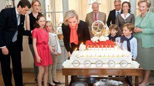 Belgian prinsessa Astrid puhaltaa syntymäpäiväkakkunsa kynttilöitä muun kuninkaallisen perheen seuratessa.