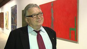 Liikemies Kyösti Kakkonen Espoon taidemuseossa. Taustalla öljyvärimaalauksia.