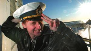 Sami Aaltonen hymyilee ja näyttää voitonmerkkiä kameralle laivan kannella.