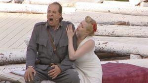 Sotilas oopperan lavalla lauluroolissaan, vaaleapukuinen neito pitää hänen olkapäästään kiinni.