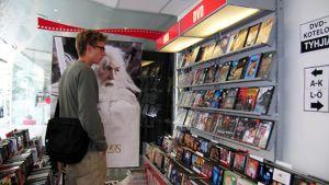 Nuori miespuolinen asiakas katselee myynnissä olevia dvd-elokuvia elokuvien erikoiskaupassa.