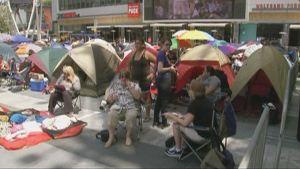 Ihmisiä ja telttoja kadulla