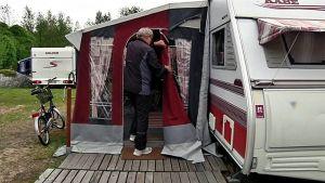 Mies menossa sisälle asuntovaunuun leirintäalueella.