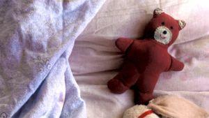 Unilelu (nalle) sängyllä