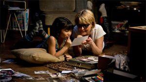 Äiti ja lapsi katselevat valokuvia lattialla