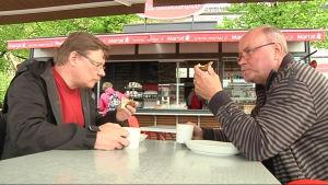 Miehet syövät karjalanpiirakoita ja munavoita Marttakahviossa Joensuun torilla.