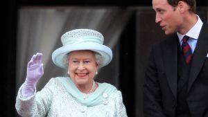 Kuningatar Elisabet II vilkuttaa Buckinghamin palatsin parvekkeelt, vierellä prinssi William.