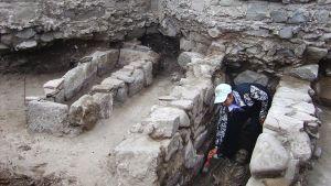 Arkeologi tutkii hautaa puhdistamalla maata sudilla.