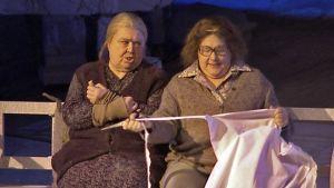 Kaksi vanhaa naista istuu penkillä näyttämöllä