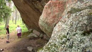 Kuva kalliosta metsässä. Taustalla suomenuskovaisia.