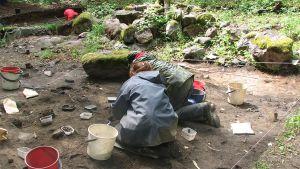 Kaksi sadetakkeihin pukeutunutta ihmistä selin kaapii maata muoviämpäreihin arkeologisilla kaivauksilla