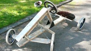 Puusta ja lastenvaunujen pyöristä rakennettu mäkiauto.