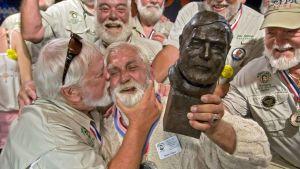Ernest Hemingway yhdennäköisyyskilpailun osanottajia. Voittaja kannattelee Hemingwayn veistosta käsissään.