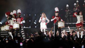 Madonna ja sotilastyyliin puettuja tanssijoita ja soittajia lavalla.