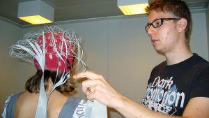Kaksi ihmistä testaa aivojen reagointia musiikkiin EEG-laitteen avulla.