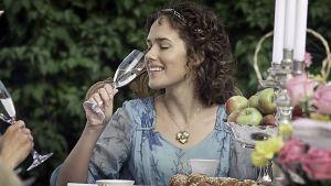 Nainen juo kuohuviiniä juhlapöydässä