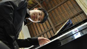 Mies pianon ääressä.