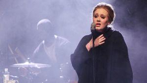 Adele laulaa lavalla, sinisen hämyn takaa näkyy rumpali.
