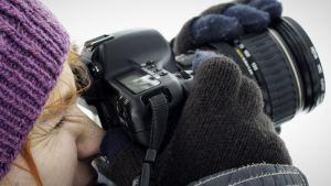 Nainen valokuvaamassa järjestelmäkameralla.