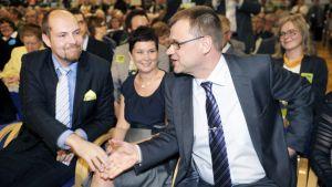 Tuomo Puumala (vas.) ja Juha Sipilä kättelevät Puumalan puolison Päivi Tiittasen yli Keskustan puoluekokouksessa Rovaniemellä 9. kesäkuuta 2012.