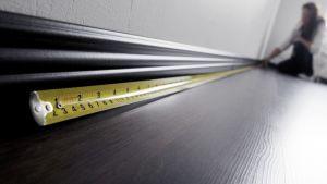 Nainen mittaa mittanauhalla asuntoa.