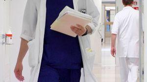 Lääkäri paperipinkka kädessä.