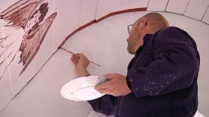 Taiteilija Raul Pohjonen maalaa Yli-Sokojan kivikirkon kattoon kirkkomaalauksia.