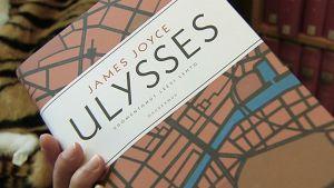 Henkilö pitelee James Joycen Ulysses-kirjaa.