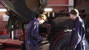 Varusmiehet huoltavat autoa Viestirykmentissä.