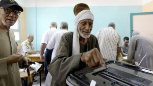 Hymyilevä egyptiläinen vanha mies jättää äänensä vaaliuurnaan.