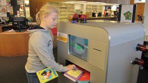 Tyttö lainaa kirjoja kirjastossa.