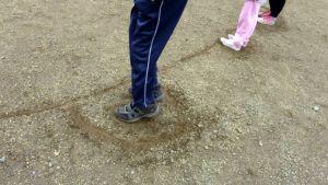 Lapsen jalat näkyvät hiekkaan piirretyssä pesässä.