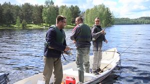 Kolme puolalaista kalastajaa seisoo soutuveneessä ja heittää virveliä.