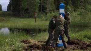 Rajamiehet pystyttämässä uutta rajamerkkiä. Taustalla venäjän rajamerkki.