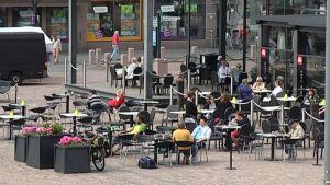 Ihmisiä Bar & cafe Paussin terassilla Kotkan torilla.