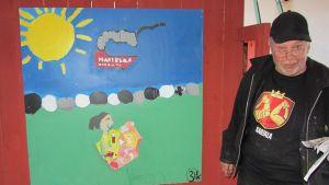 Patu Patanen koululaisten maalaaman taulun vieressä