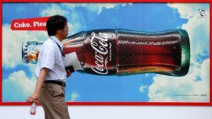 Mies kävelee Coca-Cola -mainoksen ohitse Tokion keskustassa.