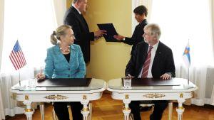 Hillary Clinton ja Erkki Tuomioja istuvat pienten pöytien ääressä.