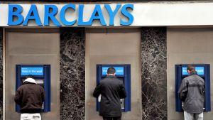 Miehiä nostamassa rahaa Barclays-pankin automaateilta.