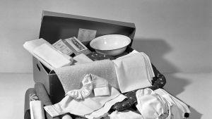 1950-luvun äitiyspakkauksen sisältöä.