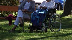 Sairaanhoitajan valkoiseen asuun pukeutunut hoitaja istuu puistossa pyörätuolissa istuvan vanhuksen kanssa.