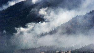 Maastopaloista nousevaa savua asuintalojen taustalla vuorenrinteessä.