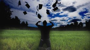 Mies pellolla heittämässä papereita ilmaan.