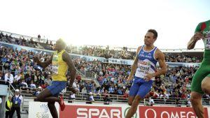 Juoksijat juoksevat olympiastadionin kaarteessa.