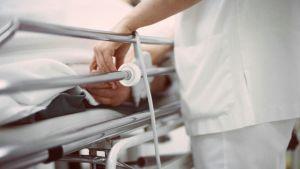 Sairaanhoitaja pitää potilasta kädestä.