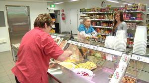 Kuvassa myyjä annostelee valmistiskiltä ruokaa asiakkaille