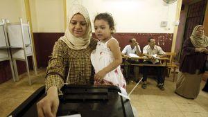 Egyptiläisnainen lapsi sylissään äänestämässä.