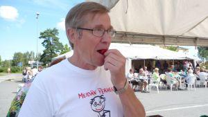 Matti Paasonen maistaa mansikkaa Mäntyharjun torilla.